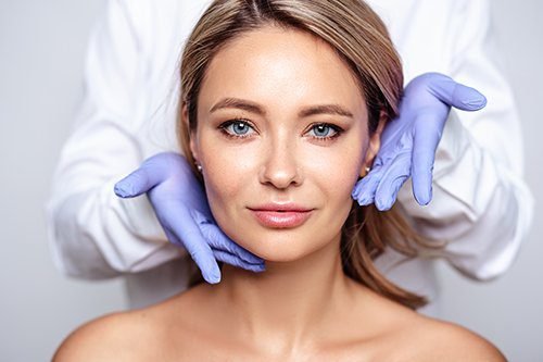 Woman's face being held by two gloved hands of skin professional.